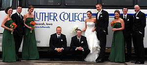 A Luther College Alumni wedding party pose for a photo with the Luther College Motorcoach.