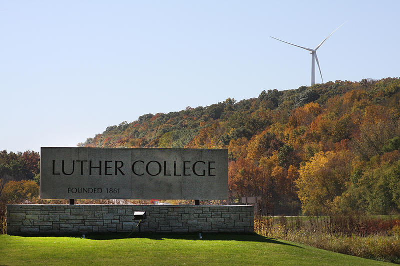 Wind turbine in the Oneota Valley with the Luther College sign