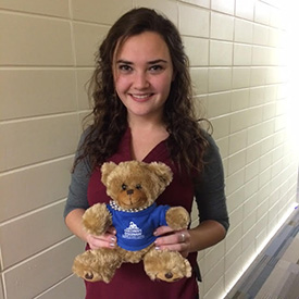 Lauren Welch holding a teddy bear from her internship at Children's Discovery Academy.
