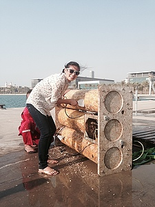 Aya Hozumi scrapes barnacles off of an acoustic echo sounder for her research in the Red Sea.
