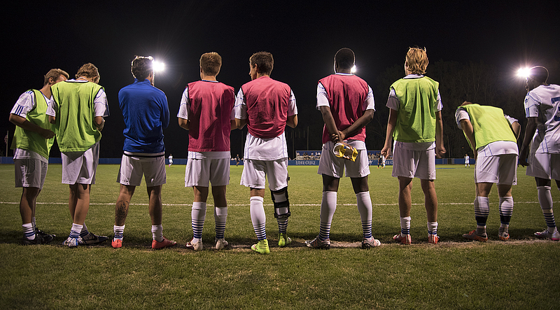 Several members of Luther's men's soccer team, standing on the sideline discussing the match.