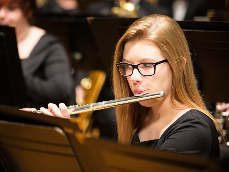 Student playing flute in concert band.