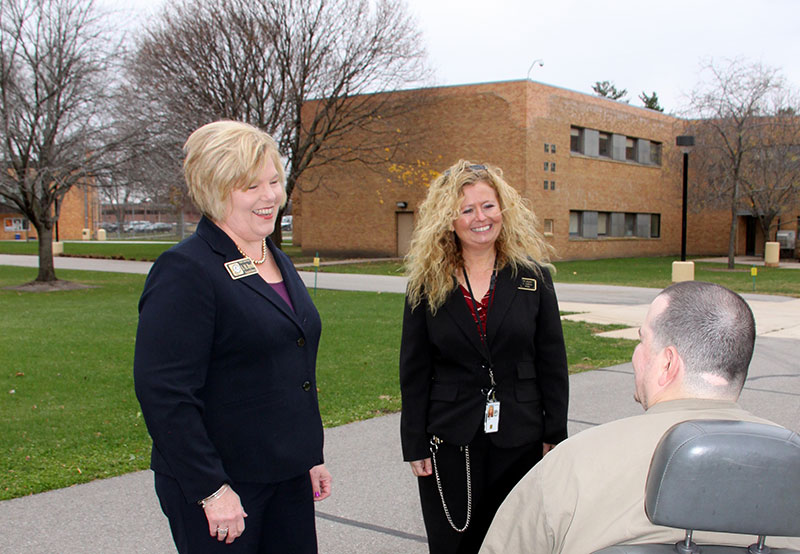 Sara Revell '84 (left) and warden Leann LaRiva talk with an inmate at the Federal Medical Center in Rochester, Minn.