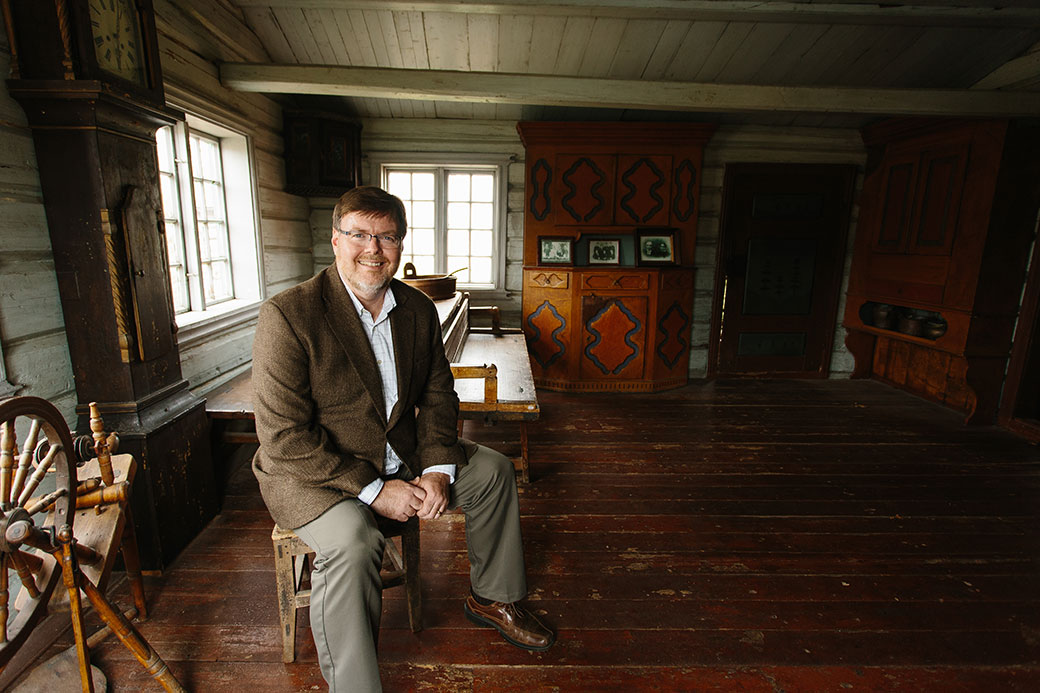 Chris Johnson '87, Vesterheim's president and chief executive officer, poses in one of the museum's outbuildings.