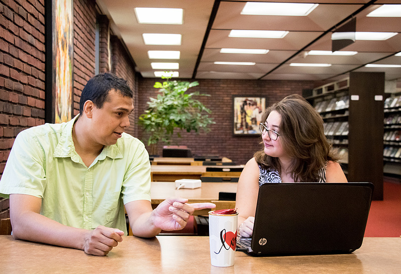 A Luther student works with a professor in Preus Library.