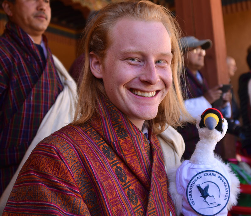 David Hecht '11 at the Black-necked Crane Festival in Gangtey, Bhutan, with the mascot of the International Crane Foundation