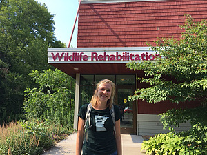 Anna stands outside the Wildlife Rehabilitation Center of Minnesota.