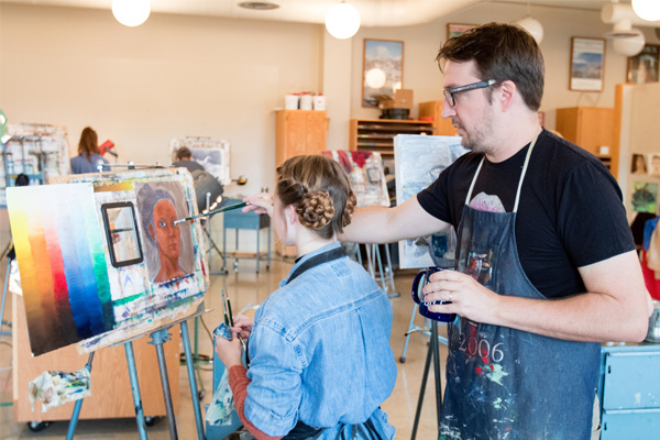 Art professor Ben Moore teaches a student in his painting class.