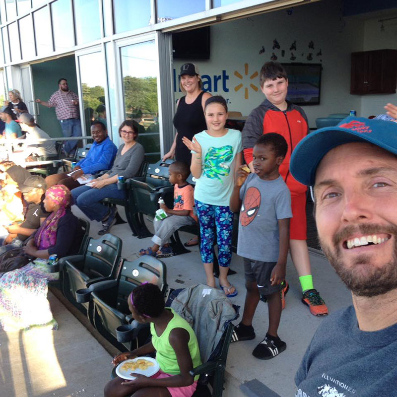 Clint Schnekloth '95 (far right), founder of Canopy Northwest refugee resettlement agency, attended an Arkansas baseball game with his family (including his wife, Amanda Grell '96, in gray), Canopy staff, and refugee families.