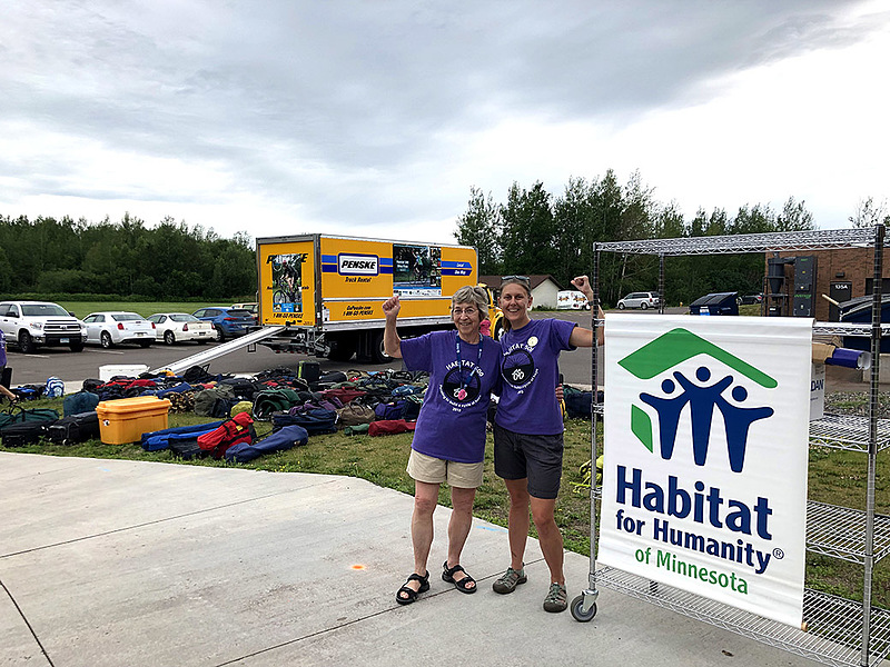 "Lilah Aas '67 (left) and Kristin Skaar '09 met through their involvement with the Habitat 500 Bike Ride. About this photo, Skaar says, ""We were unloading bags from the truck on our last day and were feeling really powerful, so we decided to flex a bit!"""