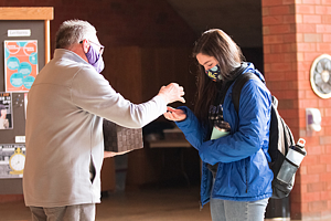 Pastor Michael Foss gives communion to a student on Ash Wednesday.
