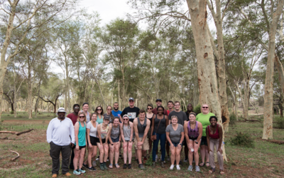 The group stands in a fever tree forest, which is a rare sighting. This is on the land that the Makuleke people won back through the land claims court.