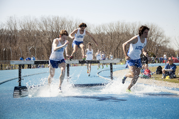 Luther runners jumping over hurdles during a meet.