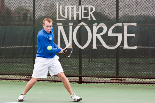 A Luther tennis player winds up for a return with the Luther Norse logo on the fence behind him.