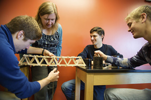 Professor Erin Flater inspects a bridge built by students in her Statics course.