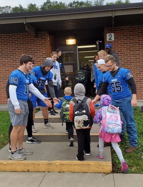 Luther football players greet students