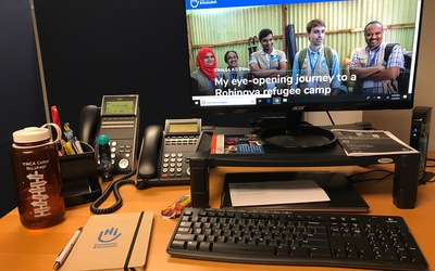 A photo of Becca's desk at Humanity and Inclusion, which shows a computer with the HI webpage open and a HI notebook that Becca was given on her first day!