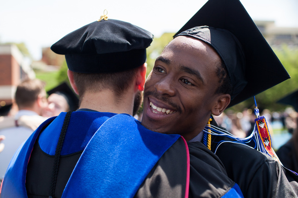 A 2014 graduate hugs a professor while wearing his cap and gown after the commencement ceremony.