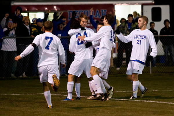 Men's soccer players celebrate on the field.
