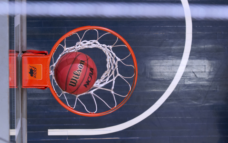 Photo of a basketball in the hoop.