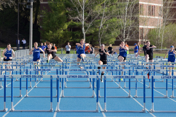 Track and field women jumping over hurdles during a meet.