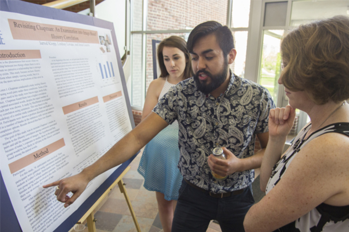 Psychology students present their work to a professor.