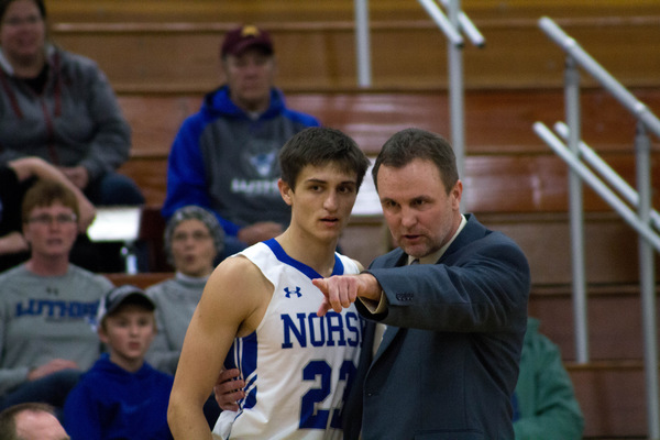 Mike Franzen, men's basketball coach, giving direction to one of the players.