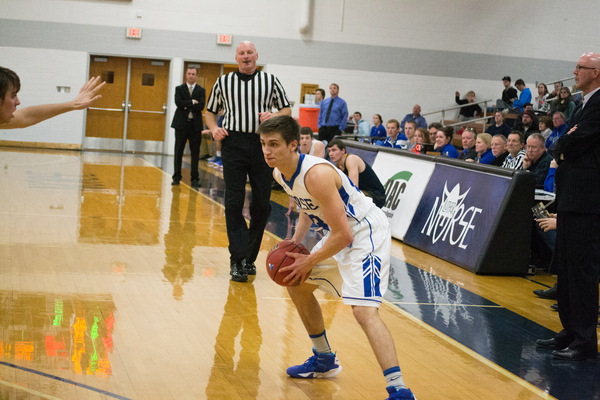 Luther basketball player on the court with the crowd watching him in the background.