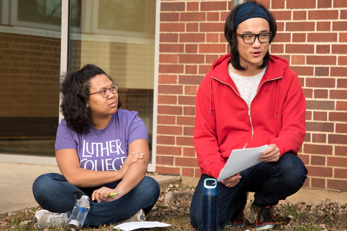 Students and their professor hold a class discussion outside.