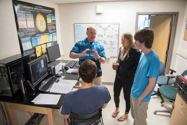 Dr. Pedlar and students discuss Belle Detector operations
