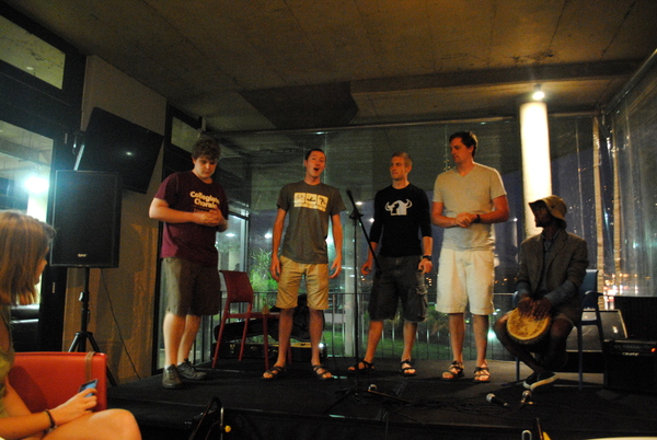 "Andrew Streck, Paul Esker, Nate Converse, and Jim Cochrane sing a song a Capella at an open mi night at the Steve Biko Center in Ginsberg.<a href=""/reason/images/526314_orig.jpg"" title=""High res"">&prop;</a>"
