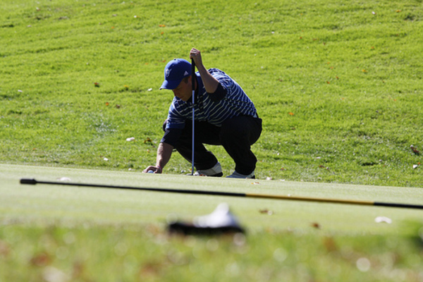 A golfer kneels on the putting green and reaches for a golf ball.