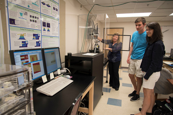 Dr. Flater demonstrates to students Megan Petzold and Keegan Danielson how the Atomic Force Microscope works.