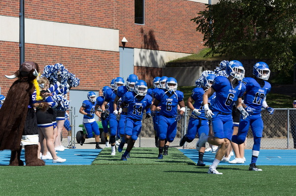 The Luther Football Team runs into Carlson Stadium.