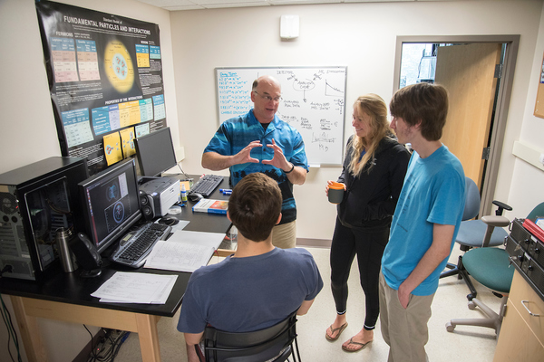 Students listen to a professor during a collaborative research over the summer.