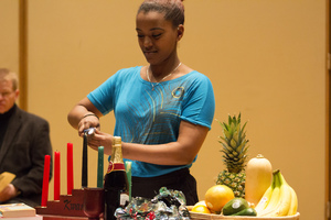 A Luther student lights a candle at the annual Kwanzaa chapel service