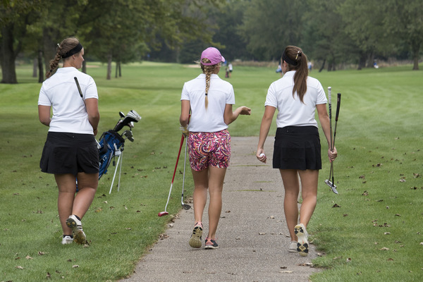 Three Luther golfers heading to the green with their golf bags and clubs.