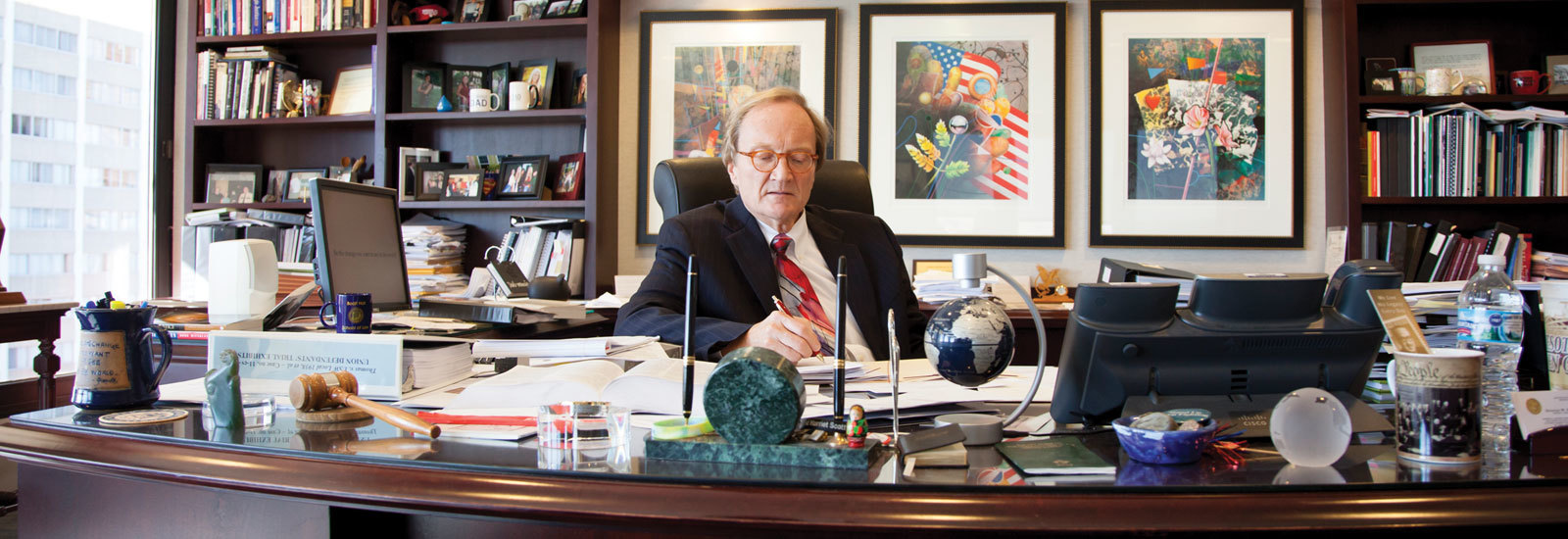 Frank works in his chambers, which are adorned with photographs, mementos, and awards from his 37-year legal career.