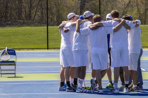 Luther tennis players in a huddle on the court.