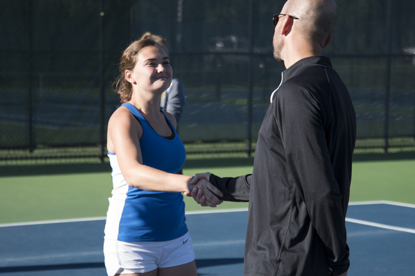A Luther tennis player shakes the hand of her coach while smiling.
