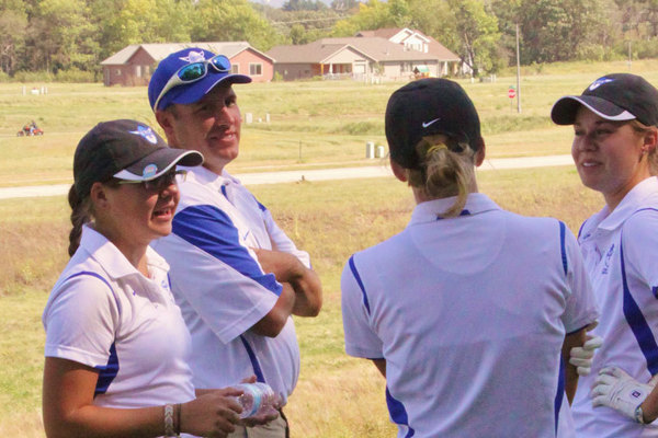Women's golf coach Eric Karius with some members of the team.