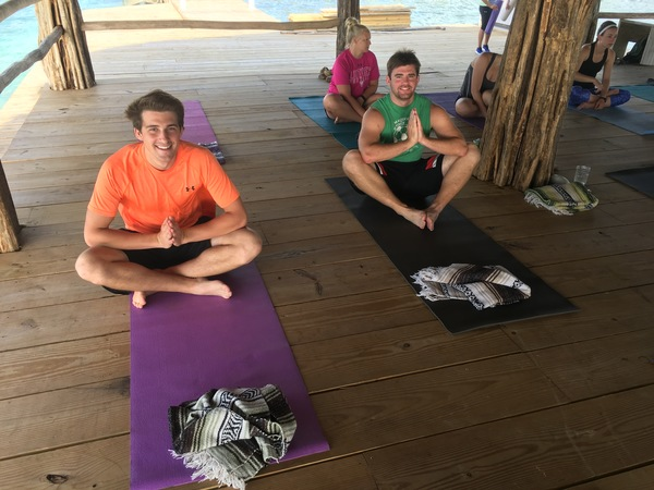 "Sophomore Freddy Kalb and Senior Tyler Regan prepare for a yoga class on the pier.<a href=""/reason/images/742457_orig.jpg"" title=""High res"">∝</a>"