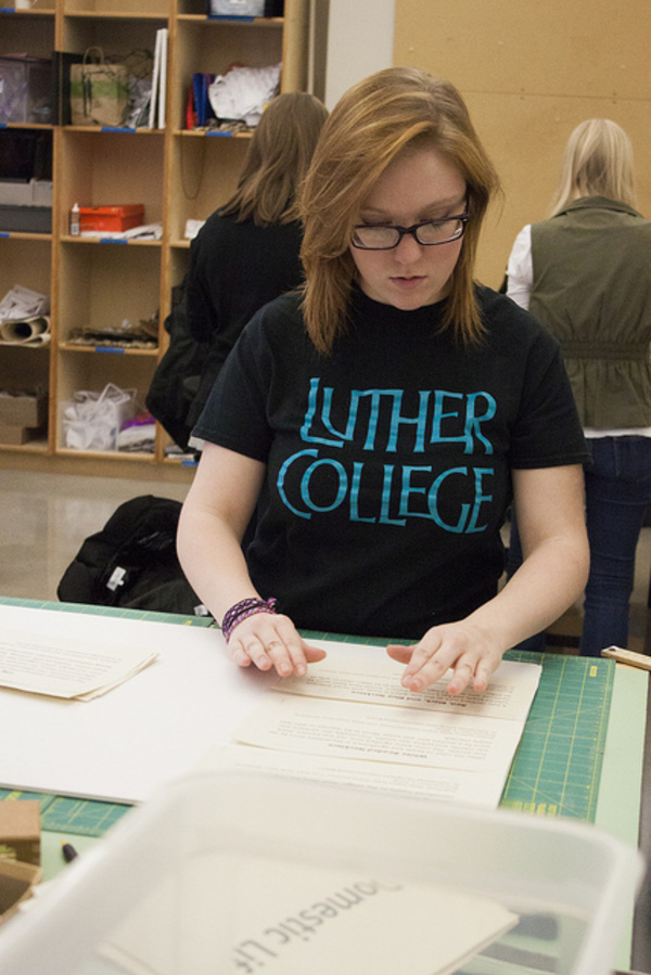 Taylor Kinley prepares exhibit labels for Olin display case.
