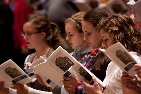 Luther students during chapel are shown actively singing and engaged in the service.