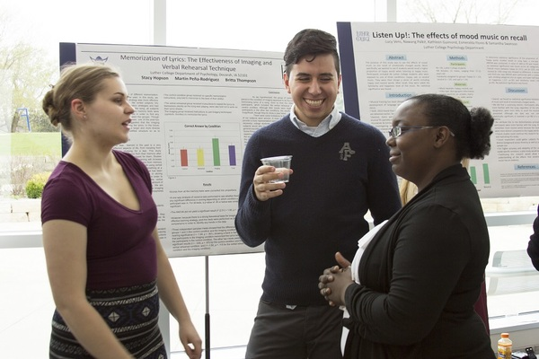 Students gather in front of a poster during Luther's annual Student Research Symposium held each May.
