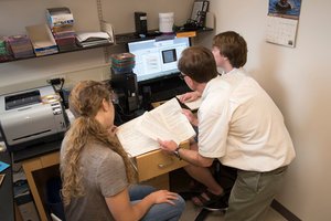 Professor Wilkerson and students Madilyn Heinke '19 and Eric Floden '18 studying star data.