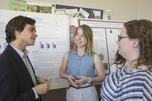 Students discussing their physics poster at the student research symposium.