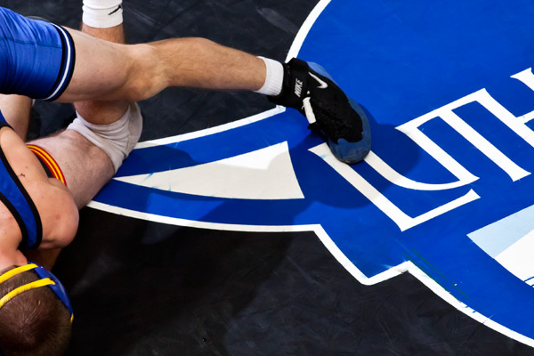 Athletes wrestle near the Luther logo.