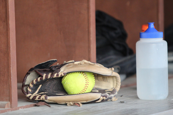 A softball inside of a glove on the bench.