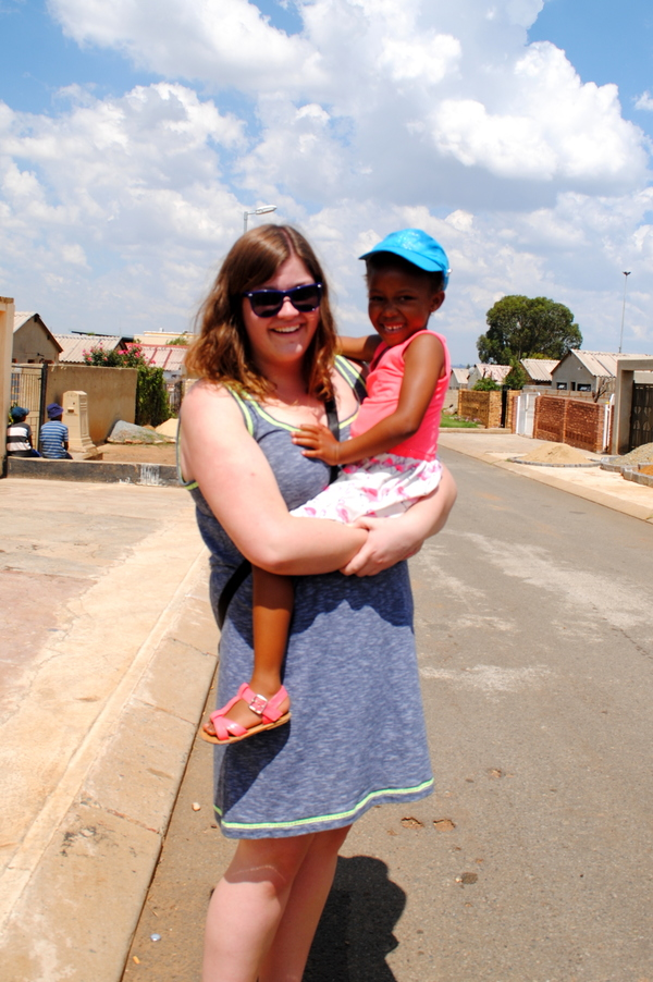 "Caitlin Olson and our new friend from Soweto, 5-year-old resident of Soweto Sanona, pose in the street of the township.<a href=""/reason/images/522596_orig.jpg"" title=""High res"">&prop;</a>"